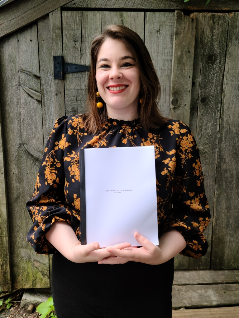 """Bailey Merlin in a black and yellow shirt, black pants, and yellow earrings holding a white manuscript with the words """"A LOT OF PEOPLE LIVE IN THIS HOUSE"""" on it."""
